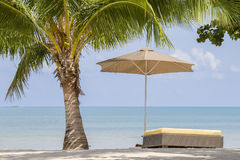 Beautiful tropical beach, palm tree, sea water, umbrella and sunbed on a sunny day. Thailand Royalty Free Stock Image