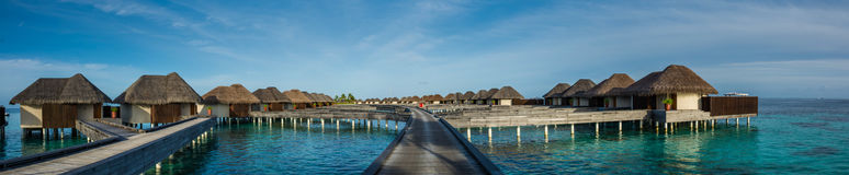Beautiful tropical beach panorama of water bungalos with bridge near the ocean at Maldives Stock Photos