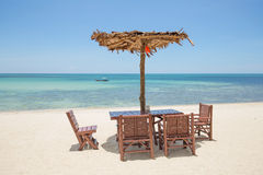 Beautiful tropical beach. Beach umbrella and wooden table and chairs on the beach. Island Koh Phangan, Thailand Stock Photo