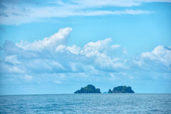 Beautiful tropical blue ocean and clouds on sky with two islands Stock Image