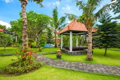 Beautiful tropical garden with swimming pool, palms and flowers stock photo