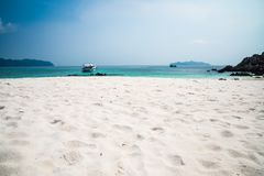Beautiful tropical island white sand beach blue sky sunny day - Royalty Free Stock Image