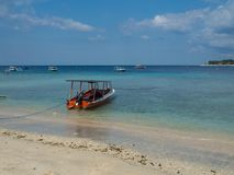 Beautiful tropical lagoon on a deserted island with boat in foreground. Gili, Indonesia, 2017. Beautiful tropical lagoon on a deserted island with boat in Stock Photography