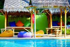 Beautiful tropical pool with thatch and colorful pads Royalty Free Stock Image