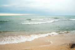 Sands beach and waves of crystal clear blue waters Royalty Free Stock Image