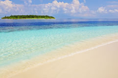 Beautiful tropical scene. With turquoise water, gentle waves and corall sand at a beach. Maldives Stock Photos