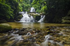 Waterfall stream in the middle of green rain forest. Beautiful tropical waterfall stream in the middle of green rain forest Royalty Free Stock Image