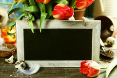 Beautiful tulips bouquet, easter eggs  and garden tools on woode Stock Image