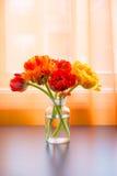 Beautiful tulips bouquet in vase on table near window Stock Photos
