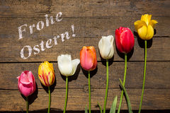 Beautiful tulips on a brown wooden table and german words Happy Royalty Free Stock Photos