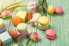 Beautiful tulips with colorful macaroons on greenery wooden back Stock Photo