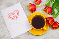 Tulips ,cup of drink and handmade card with kid`s drawing for Mother`s Day on marble background, top view. Beautiful tulips ,cup of drink and handmade card with royalty free stock photography