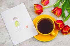 Tulips ,cup of drink and handmade card with kid`s drawing for Mother`s Day on marble background, top view. Beautiful tulips ,cup of drink and handmade card with royalty free stock images