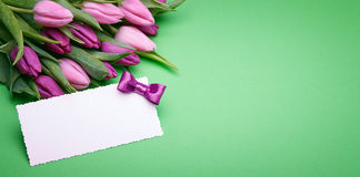 Beautiful tulips and greeting card. Greeting card, bouquet of beautiful flowers, buds of spring tulips, bow from satin ribbon, the gift set on a green background Royalty Free Stock Photography
