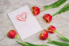Tulips and handmade card with kid`s drawing for Mother`s Day on marble background, top view. Beautiful tulips and handmade card with kid`s drawing  for Mother`s royalty free stock images