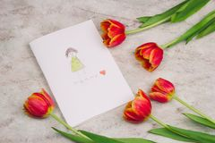 Tulips and handmade card with kid`s drawing for Mother`s Day on marble background, top view. Beautiful tulips and handmade card with kid`s drawing  for Mother`s stock images