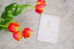 Tulips and handmade card with kid`s drawing for Mother`s Day on marble background, top view. Beautiful tulips and handmade card with kid`s drawing  for Mother`s royalty free stock photos