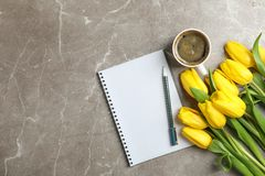 Beautiful tulips with notebooks and cup of coffee on light background stock photos