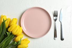 Beautiful tulips and plate with utensils for Mother`s Day on light background stock images
