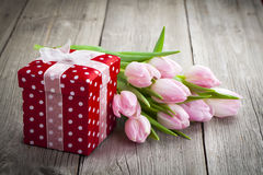 Beautiful tulips with red polka-dot gift box. Happy mothers day, romantic still life, fresh flowers. on wooden background Royalty Free Stock Photos