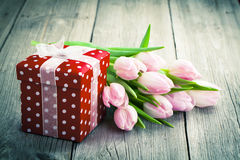 Beautiful tulips with red polka-dot gift box. Happy mothers day, romantic still life, fresh flowers. on wooden background Stock Photos