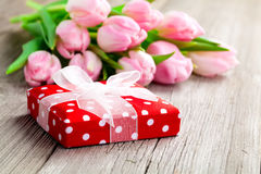 Beautiful tulips with red polka-dot gift box. royalty free stock images
