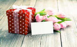 Beautiful tulips with red polka-dot gift box. Royalty Free Stock Photos