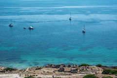 Beautiful turquoise blue sea with yachts. In the background. Part of Corinthian ruins of Tharros village can be seen in the foreground.. Shot in Sinis peninsula Stock Photos