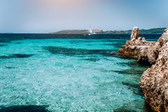 Beautiful turquoise cozy bay surrounded by white cliffs. White yacht afar in the deep blue water. Ionian islands of stock image