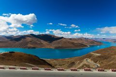Beautiful turquoise holy Yamdrok lake with himalaya range i. Beautiful turquoise holy Yamdrok lake with himalaya range,blue sky and white clouds in background Stock Photo