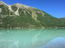 Beautiful turquoise Kucherla lake. Reflection of mountains in the water. Summer vacation in the mountains. Arrow image formed by. Reflection in the water stock photography