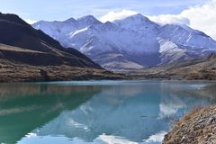 Beautiful turquoise lake in the middle of snow-covered mountains on a Sunny autumn royalty free stock image