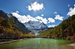 Beautiful turquoise lake in sunny day with rock mountain and blue sky background with flare light. At Yading National Reserve, Shangri la, Sichuan, China Royalty Free Stock Photos