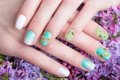 Beautiful turquoise manicure with crystals on female hand. Close-up. Picture taken in the studio Stock Images