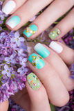Beautiful turquoise manicure with crystals on female hand. Close-up. stock photos