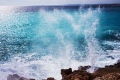 Beautiful turquoise sea, the mountains in the haze and the embankment of the Promenade des Anglais on a warm sunny day. Waves breaking on the rocks. Splashing royalty free stock photo