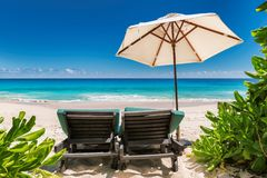 Umbrella on beach chairs on a tropical beach. Beautiful turquoise waters of Caribbean sea and Umbrella on beach chairs on tropical beach. Holiday and vacation Stock Images