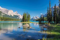Spirit Island in Maligne Lake, Jasper National Park, Alberta, Canada. Beautiful turquoise waters of the Maligne Lake with snow-covered peaks above it in Rocky Stock Photo