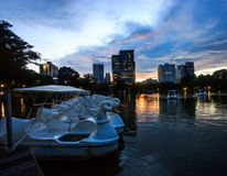 Beautiful Twilight Lake View of Lumpini Park with driving duck boat and modern buildings as background. Royalty Free Stock Photo