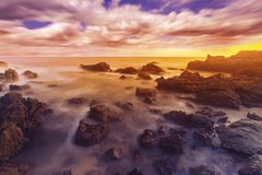 Beautiful twilight of seascape, Sunset in Thailand. Scenic view of rocky beach, Long exposure of the wave during sunset on the beach royalty free stock photography