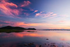 Beautiful twilight sky above a tropical lake, gently light pink clouds against the blue sky at dusk. Defocus. Beautiful twilight sky above a tropical lake stock photo