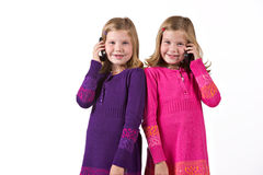 Beautiful twin girls on cell phones Royalty Free Stock Images