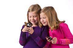 Beautiful twin girls text messaging Royalty Free Stock Photos