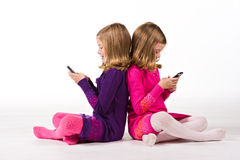 Beautiful twin girls text messaging Stock Images