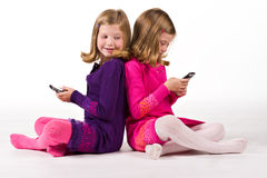 Beautiful twin girls text messaging Royalty Free Stock Photos