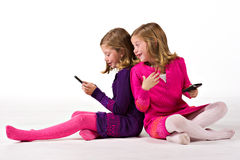 Beautiful twin girls text messaging Stock Photography