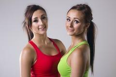 Beautiful twin sisters. Cute happy twin sisters wearing sportswear, taken on a gray background Stock Photography