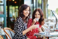 Beautiful twin sisters drinking coffee Stock Image