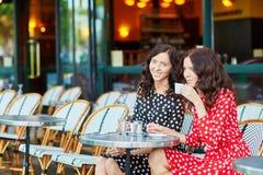 Beautiful twin sisters drinking coffee Royalty Free Stock Image