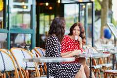 Beautiful twin sisters drinking coffee Royalty Free Stock Photography